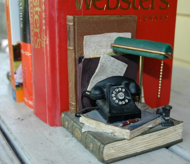"""...a dial phone, banker's lamp and """"book"""" titled Words and Phrases."""