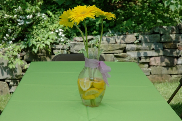 I offset the lemons and limes and yellow Gerber Daisies with a lavender ribbon around each vase.