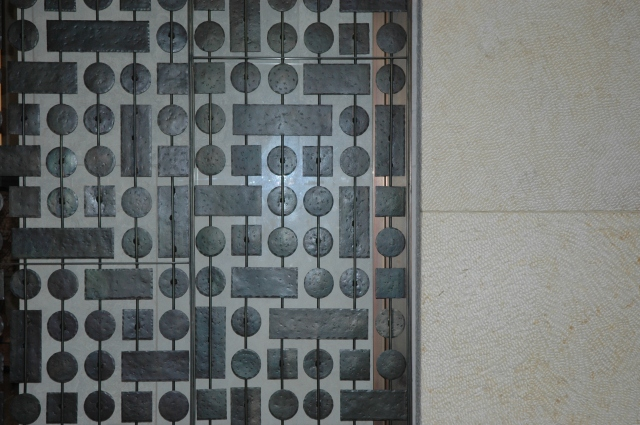"""Iron """"screen"""" next to concrete walls."""
