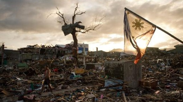 A-man-walks-along-as-the-national-flag-of-the-Philippines-flies-over-the-rubble-of-destroyed-homes-in-Tacloban-AFP-1, Agence France-Presse