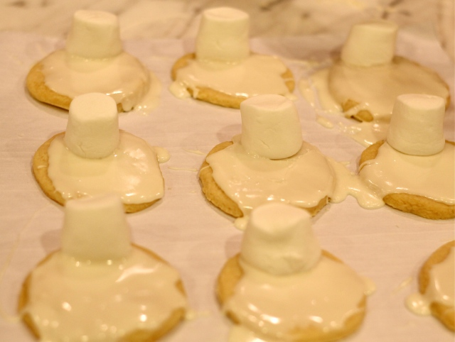 "Place one marshmallow on top of each ""snowman body.""  Lightly press on marshmallow so it sticks to cookie icing."