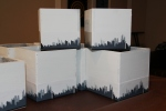 "Three 5"" x 5"" boxes were lined up on oval tables. One 6"" x 6"" box was set in the center of round tables."
