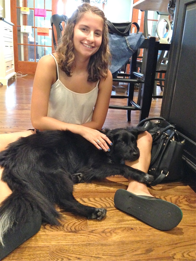 Teen daughter pets Lucy. Lucy reaches out and touches back.