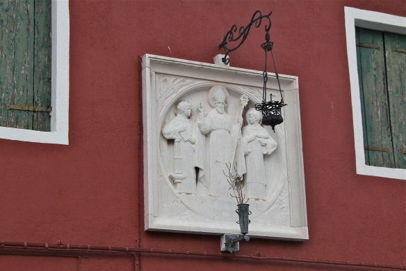 Many houses and buildings are adorned with religious wall plaques.