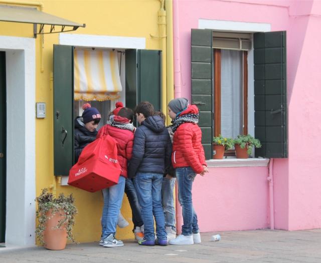 School boys meeting by a first floor window.