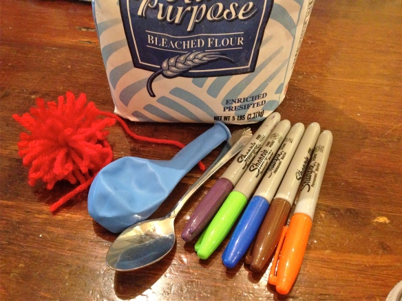 Supplies: a balloon, flour, spoon, permanent markers, pom-pom optional