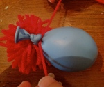 2. Knot balloon closed. Draw on face. Tie pom pom to balloon under the knot.