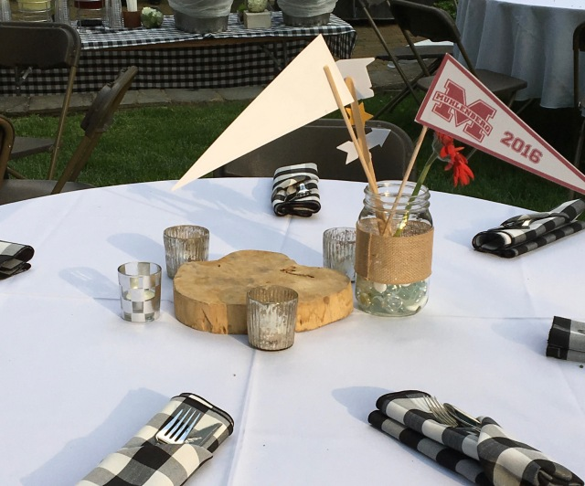 Add tea lights and citronella candles to the tables. The caterer used wooden blocks to raise small flower arrangements.