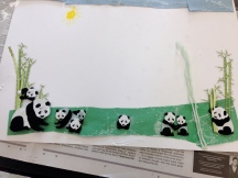 This minimalist picture places the pandas firmly on the snowy grass. Bamboo grows tall with green yarn.