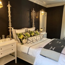 Black grasscloth walls are set against white furniture and finishes and accented with leaf green accessories. Kristin Badolato of Kristin Ashley Interiors created an unexpectedly serene guest bedroom.